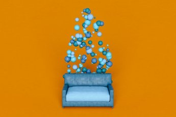 Blue spheres and sofa against orange background