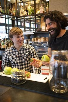 Male bartender laughing while holding fresh fruit by trainee at bar counter