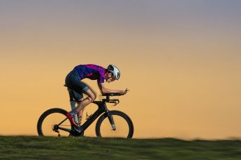 Male sportsperson triathlon riding bicycle on land during sunset