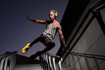 Young African man with headphones jumping at staircase