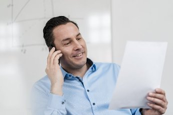 Male professional talking on smart phone while holding document at workplace