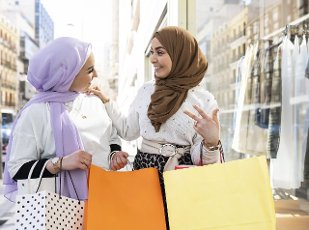 Surprised woman looking at female friend while shopping in city
