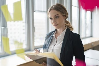 Female professional planning business strategy while writing in diary at office