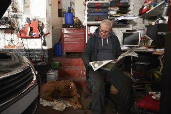 Senior male auto mechanic reading newspaper while sitting in garage