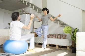 Woman teaching yoga to man sitting on fitness ball at in living room at home
