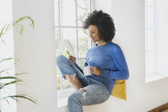 Young woman with coffee cup reading book while sitting at window sill