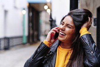 Cheerful young woman squinting while talking on mobile phone in city