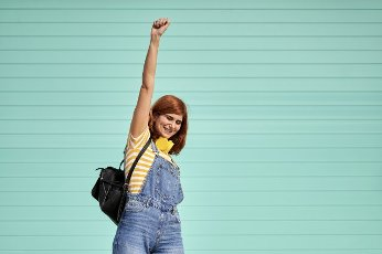 Redhead woman making victory gesture in front of turquoise blue wall