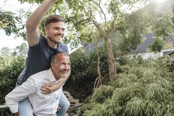 Father giving piggyback ride to cheerful son in backyard