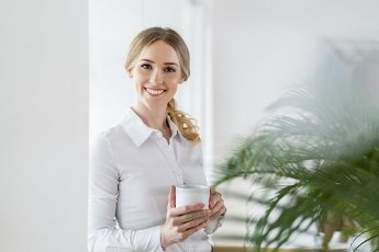 Smiling beautiful female professional holding coffee mug in office