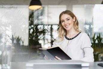 Smiling female entrepreneur holding diary at desk