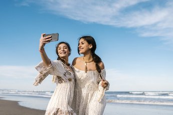 Young smiling woman taking selfie with friend through mobile phone during sunny day