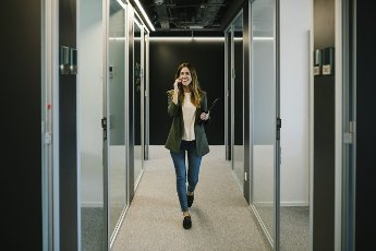 Confident businesswoman talking on smart phone while walking in corridor at office