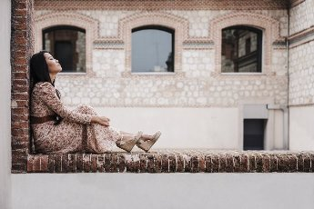 Mid adult woman relaxing while sitting on retaining wall in city
