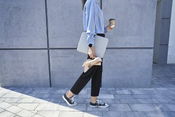 Businesswoman holding laptop and high heels while walking on footpath
