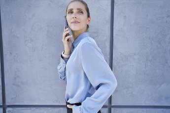Businesswoman looking away while talking on mobile phone by wall