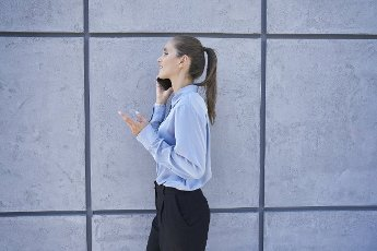 Businesswoman talking on mobile phone while walking by wall