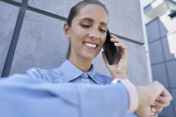 Smiling businesswoman checking smart watch while talking on mobile phone