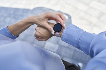 Businesswoman using smart wristwatch while standing on footpath