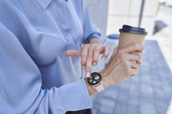 Businesswoman holding disposable coffee cup while using smart wristwatch