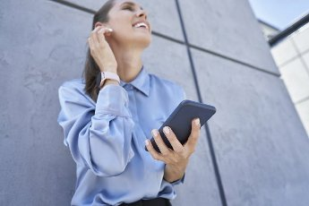 Businesswoman holding mobile phone while standing in front of wall
