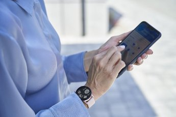 Businesswoman with smart wristwatch using mobile phone
