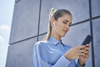 Businesswoman with wireless in-ear headphones using mobile phone by wall
