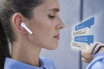 Businesswoman with in-ear headphones using smart wristwatch
