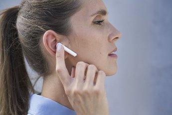 Businesswoman with wireless in-ear headphones by wall