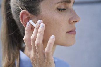 Businesswoman touching wireless in-ear headphones