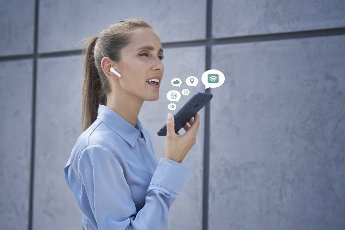 Businesswoman with wireless in-ear headphones talking mobile phone
