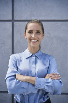 Confident businesswoman standing with arms crossed in front of wall
