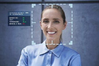 Smiling businesswoman with facial recognition technology in front of wall