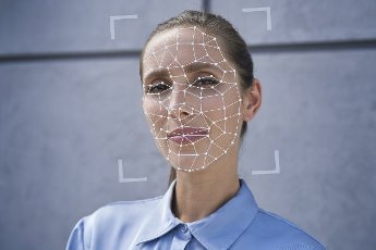 Businesswoman with facial recognition biometrics in front of wall