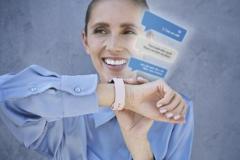 Smiling businesswoman using smart watch in front of blue wall