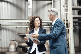 Businesswoman using digital tablet while discussing with colleague in front of industrial building