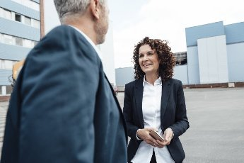 Smiling businesswoman talking with colleague while standing on footpath