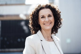 Smiling mature businesswoman in front of industry