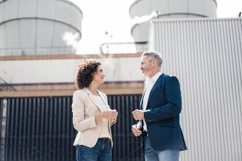 Businessman talking with colleague while standing in front of industrial building