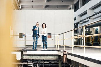 Businessman explaining colleague while standing by railing in industry