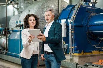 Male and female expert using digital tablet while standing at power station