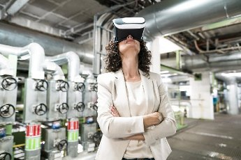 Businesswoman with arms crossed using virtual reality headset at power station
