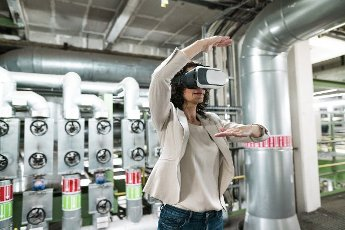 Female expert gesturing while using virtual reality headset in industry