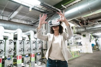 Businesswoman using virtual reality headset while standing in workshop