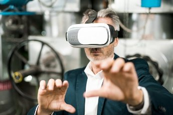 Businessman gesturing while using virtual reality headset at workshop
