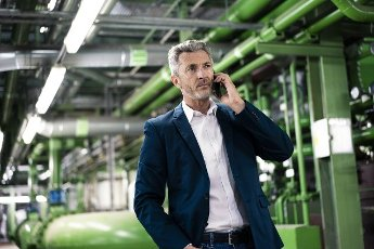Businessman talking on smart phone while standing in industry
