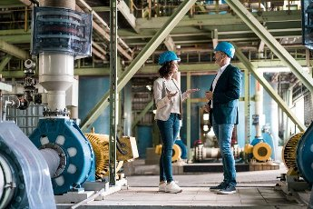 Male and female expertise having discussion while standing at power station