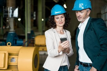 Inspector team with hardhat using mobile phone while standing in industry