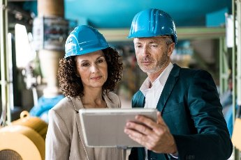 Expertise team with hardhat using digital tablet in industry
