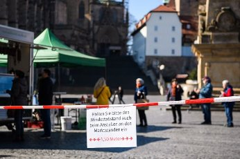 (200401) -- ERFURT (GERMANY), April 1, 2020 (Xinhua) -- A sign to remind people of keeping a distance is seen at a market in Erfurt, central Germany, on April 1, 2020. Germany will extend the restrictions on social contacts to April 19 at the earliest, in a bid to contain the COVID-19 spreading, Chancellor Angela Merkel said following a video conference with minister-presidents of all 16 federal states. (Photo by Kevin Voigt/Xinhua)